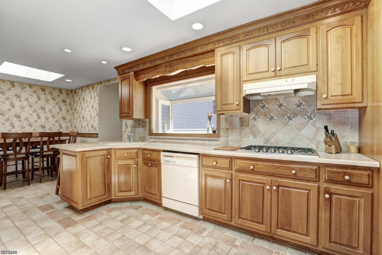 Recessed lighting, tile flooring, tile backsplash, decorative moldings, garden window.