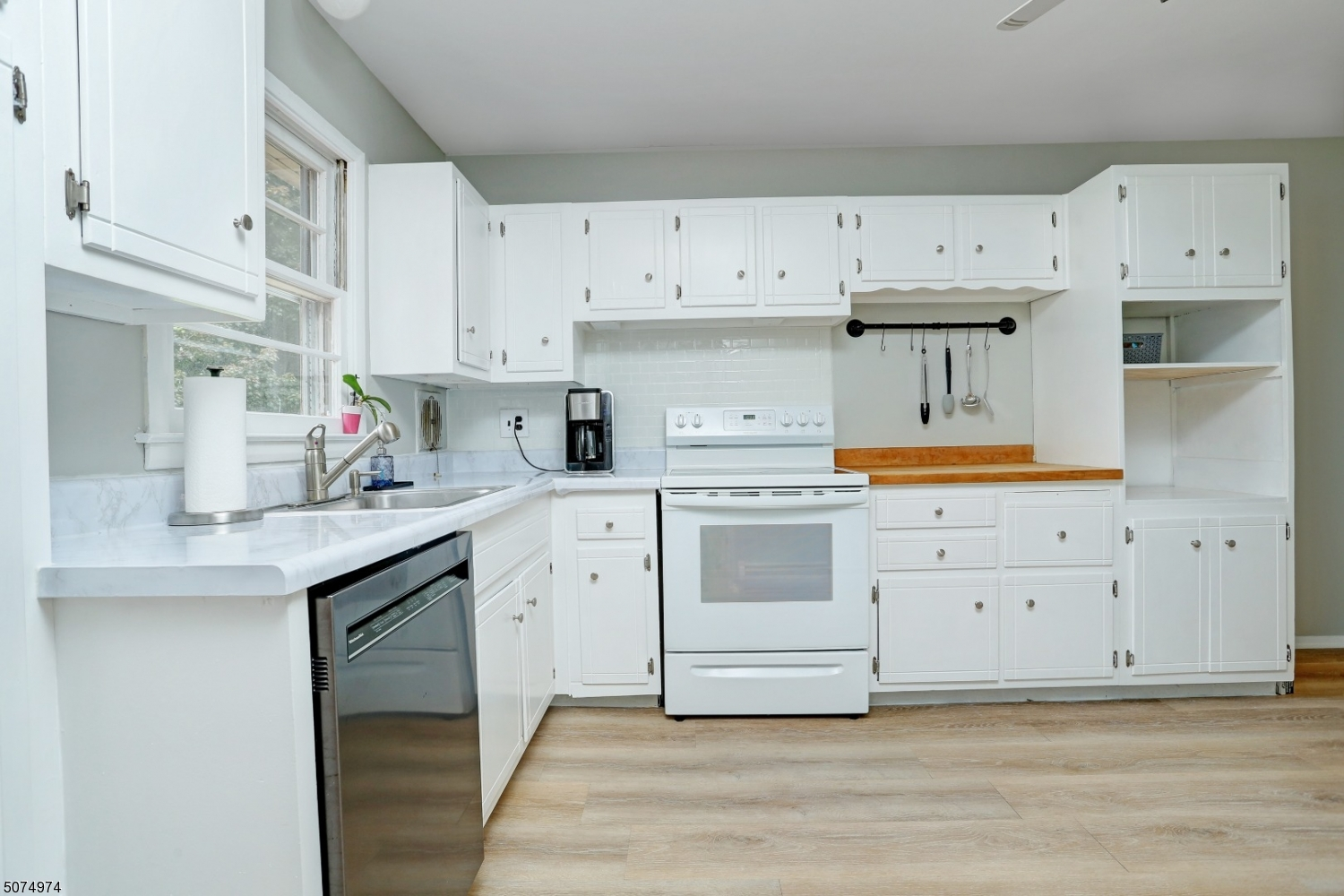 New wood-like laminated floors are just one of the new amenities this kitchen has to offer.  Electric range/oven, Kitchen Aid Dishwasher, GE fridge/freezer, tile-like backsplash and laminate counter tops with stainless steal sink complete this kitchen!