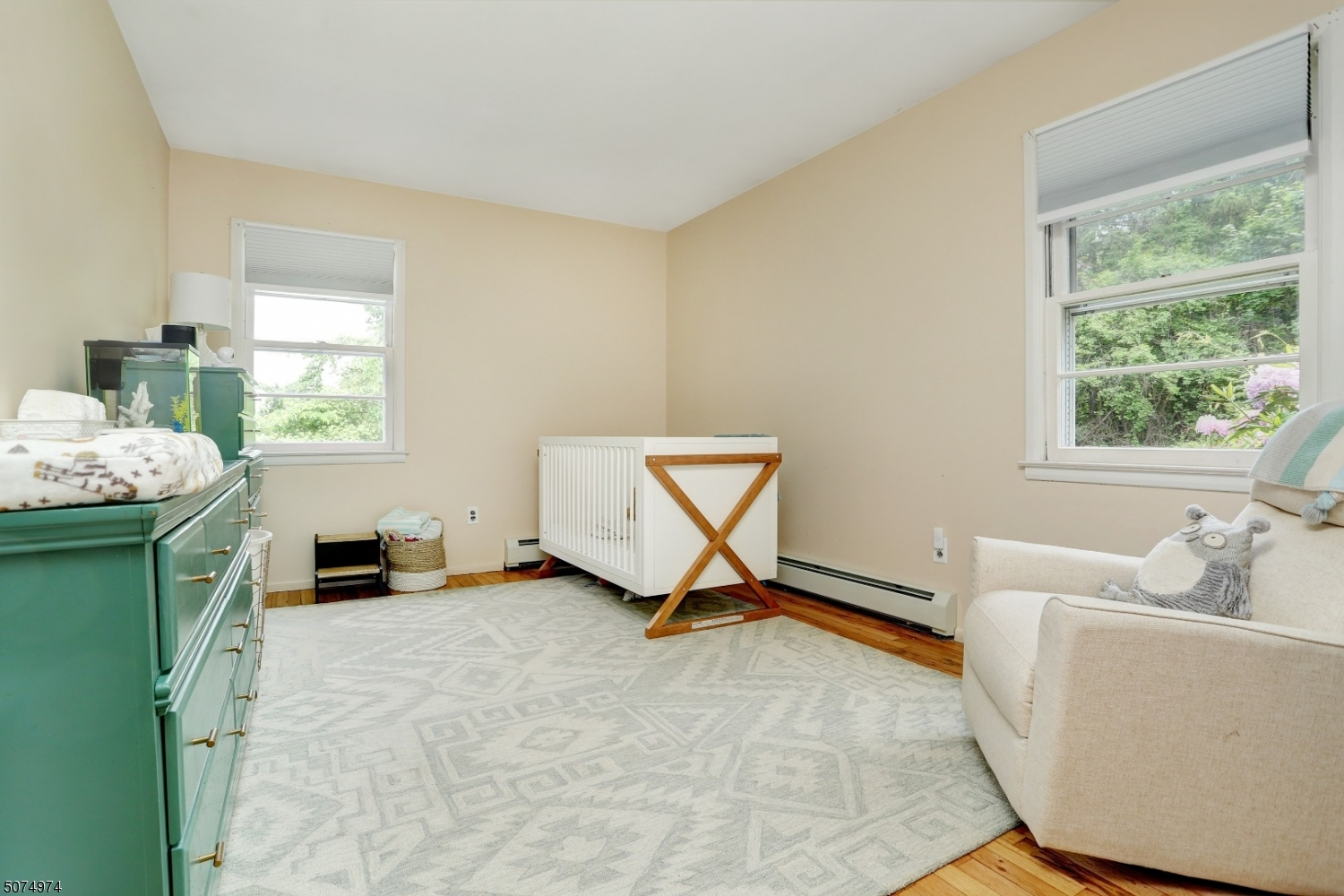 Two double-hung windows with newly refinished hardwood floors throughout the room.