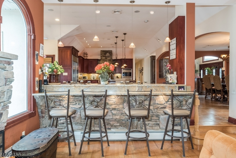 The opposite side of the Kitchen has bar-style countertop seating. It's the perfect setting for casual eating as well as a spot for guests to relax while you finish the prepping!