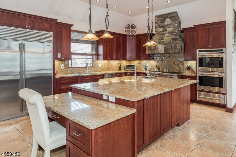 Large custom center island w/granite countertop also has an additional sink, storage rm & features a matching desk that effortlessly blends in. The wine refrigerator & microwave make a perfect addition to this c/island and compromise no Kitchen space!