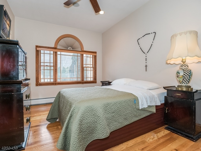 Comfortably sized Bedroom features shiny hardwood floors, oversized window and ceiling fan that helps circulate the air on hot days and nights.