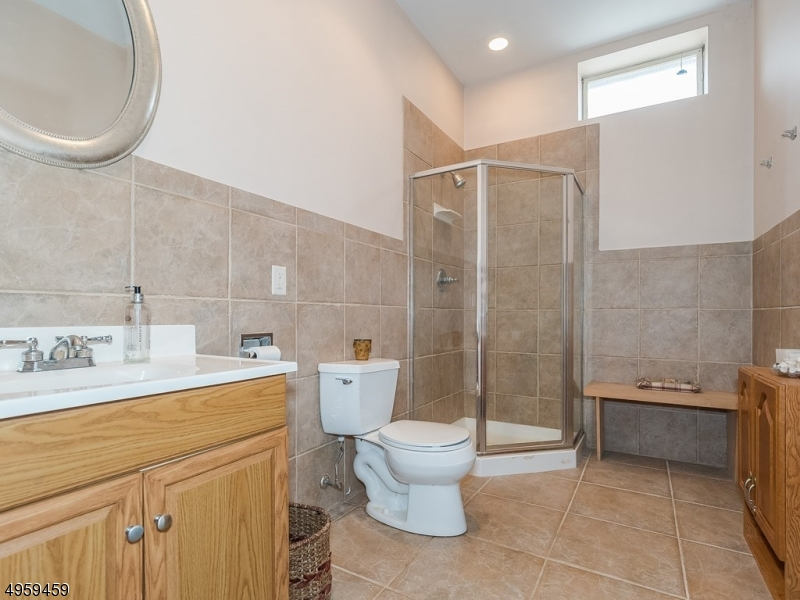 Bright and light full Bathroom with maintenance free wall/floor tiles and luxury walk-in stand up shower.