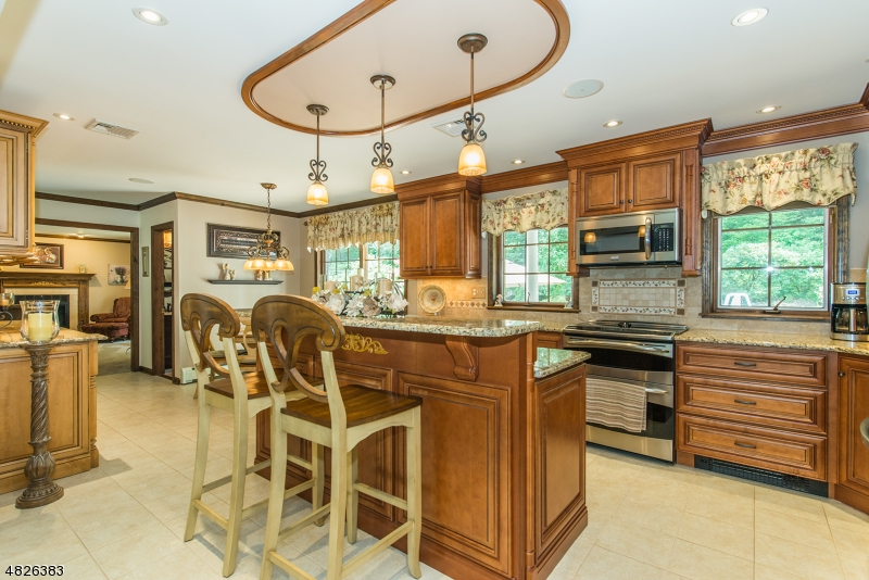 Upscale stainless steel appliances and custom lighting accent this gourmet kitchen.....