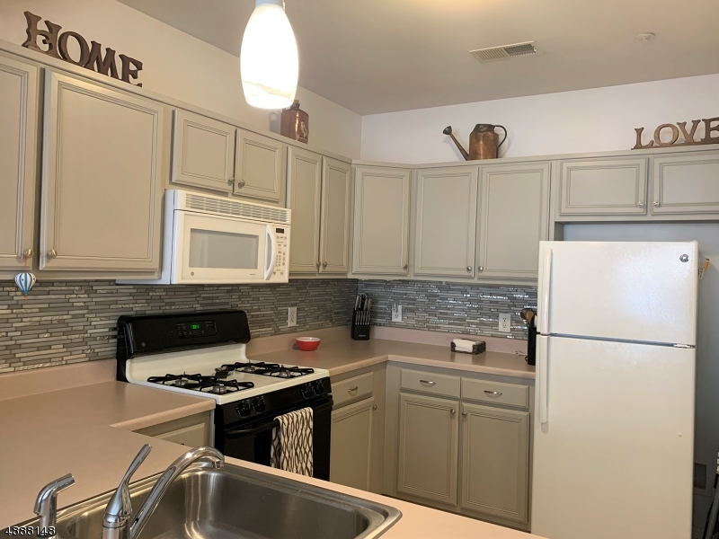This kitchen is nicely updated and is spotless.  You'll appreciate how clean and well maintained this kitchen is.   The backsplash offers all neutral colors with current glass tile.