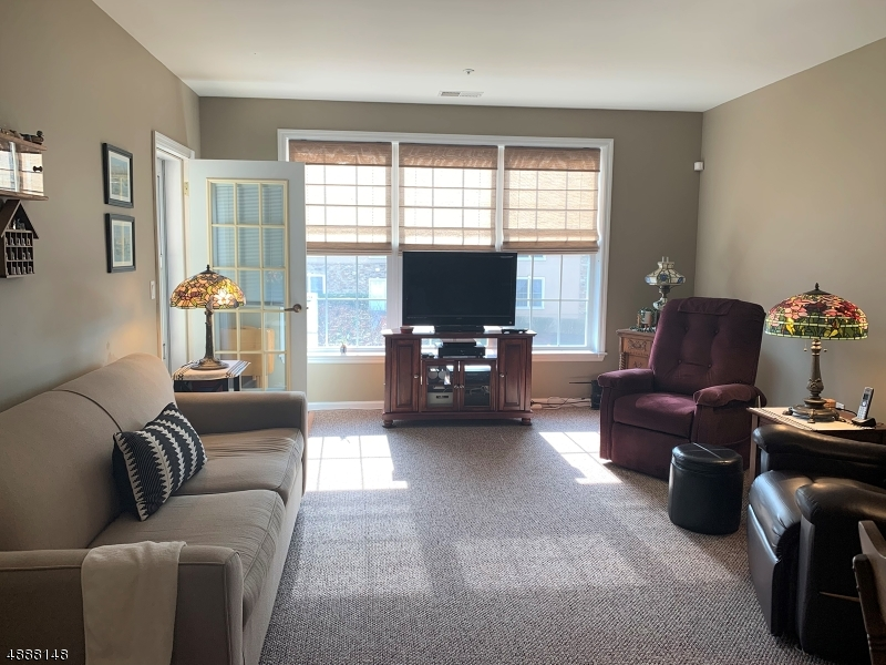 Beautiful sunlit living room, offers 3 large windows, updated neutral carpeting, and access to the balcony with glass entry and screen door.