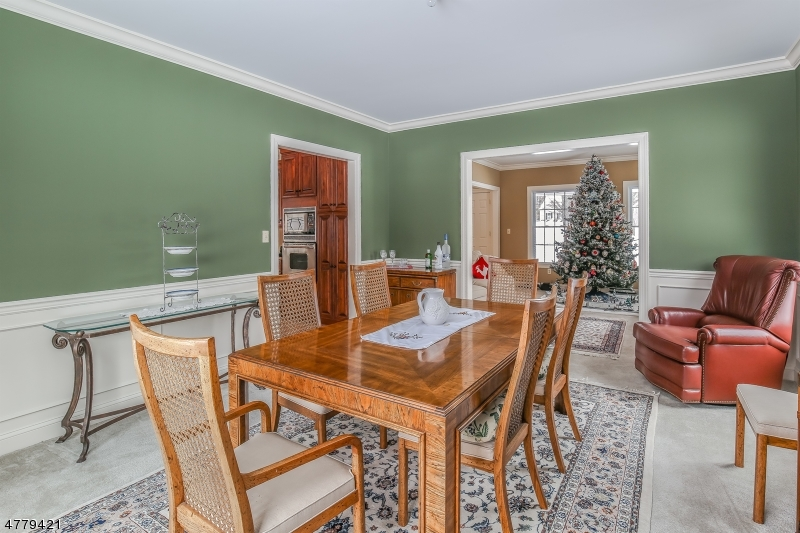 Crown molding and wainscoting enhance this nicely sized dining room that flows into the formal living room....or Christmas room!