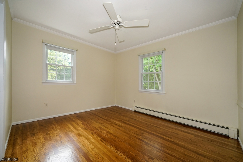 The second bedroom has hardwood floors and a lighted ceiling fan with a double closet