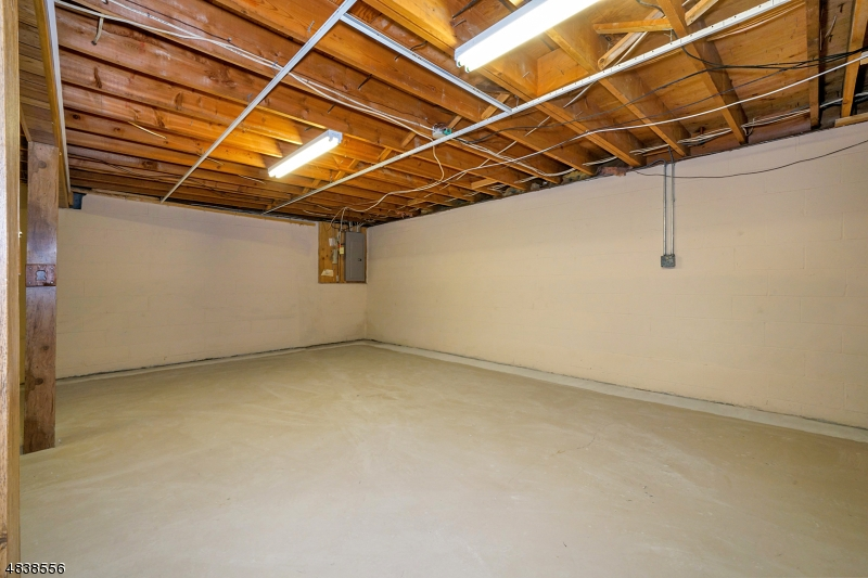 The unfinished basement has a painted floor and a workshop area.