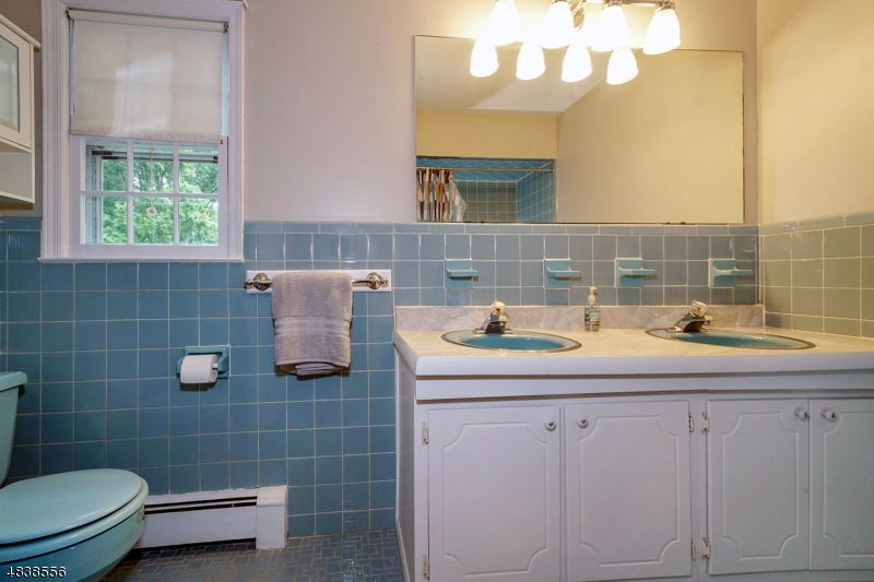 The second level hall bathroom has a tub/shower with tile flooring and two sinks.