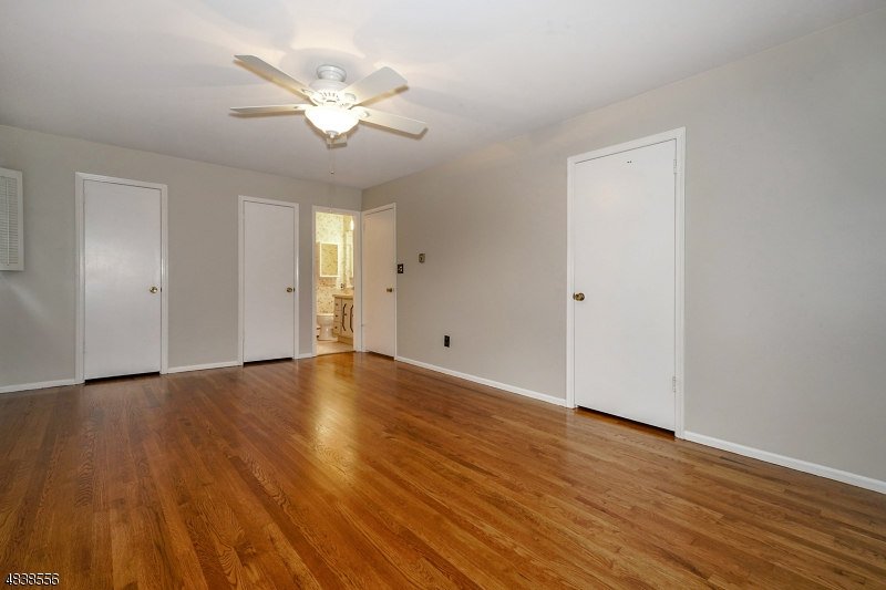 The primary suite has hardwood floors with two closets and a full bath.