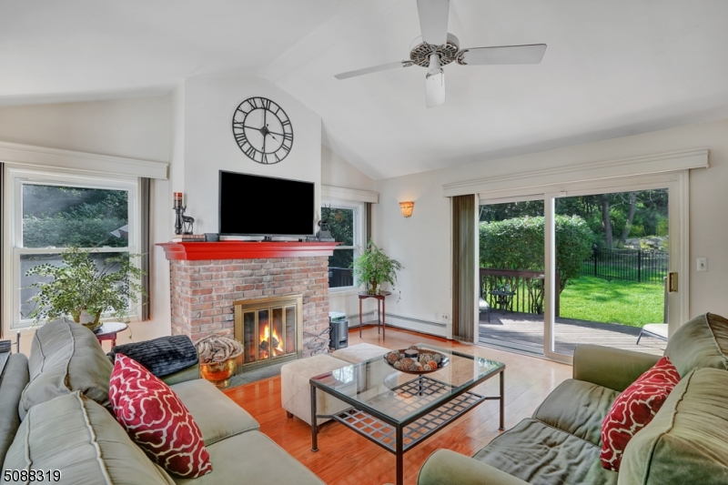 Open concept great room with vaulted ceilings and gas fireplace opens to spacious deck.