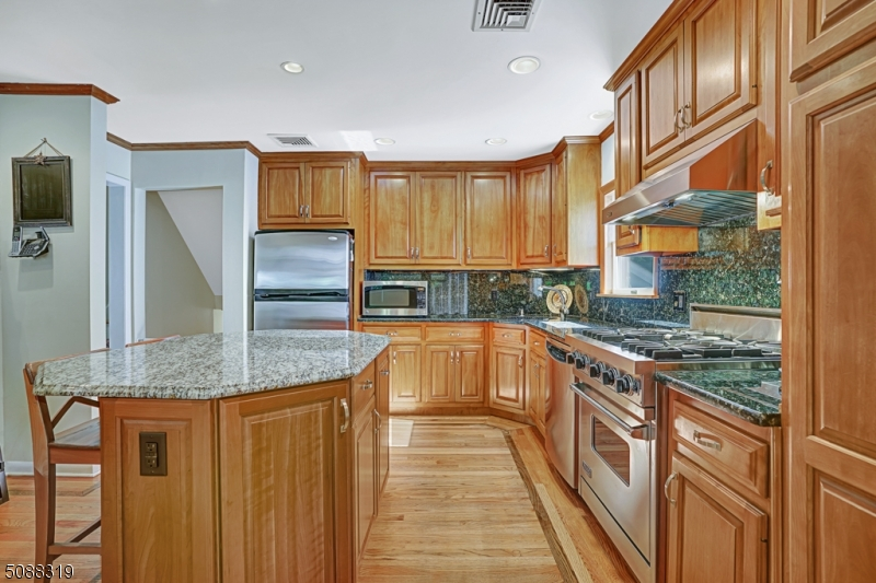 Stunning chef's kitchen w/ granite counters/island, stainless appliances, commercial grade viking range, 4-burner gas stove + pass thru to dining room.